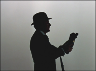 John Steed, wearing his bowler and carrying his umbrella over his arm, opens a bottle of champagne. He is backlit and in silhouette.